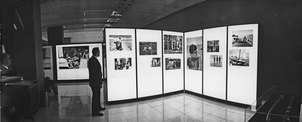 RSSPP-PH-092-P. Black-and-white photograph of an individual viewing illuminated panels that feature a series of photographs of John F. Kennedy.