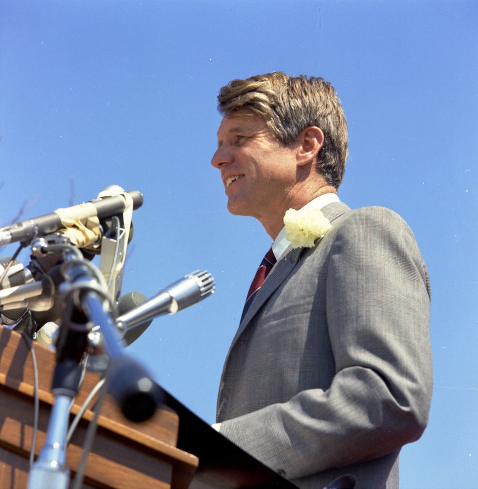 SWPC-RFK-C005-004. Color photograph of Robert F. Kennedy standing at a podium that holds several microphones.