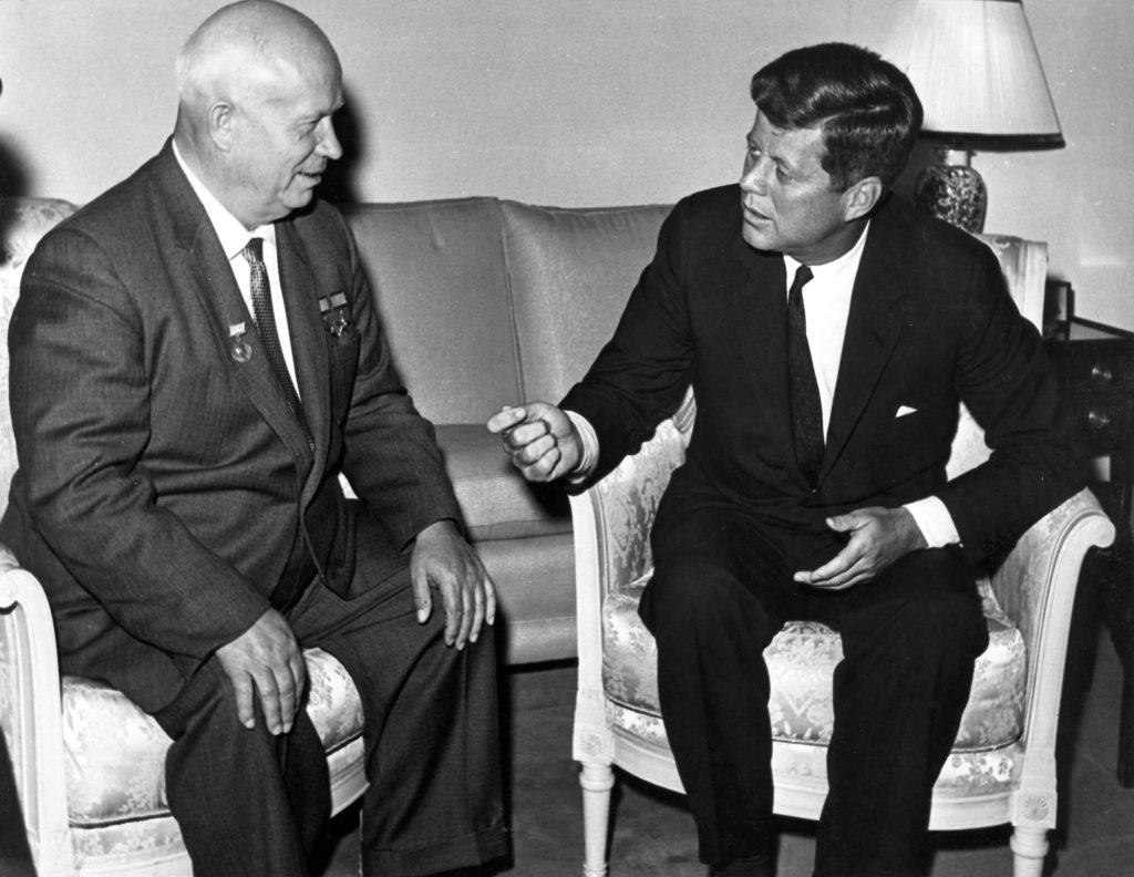 Black-and-white photograph featuring Soviet Premier Nikita Khrushchev, seated at left, looking at President John F. Kennedy, seated at right, as Kennedy gestures while speaking.