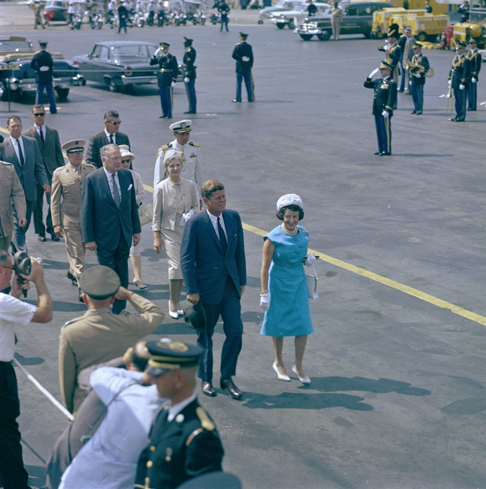 Color photograph of President John F. Kennedy and Rose Fitzgerald Kennedy walking outdoors with a group of people following, and members of the press and military looking on.